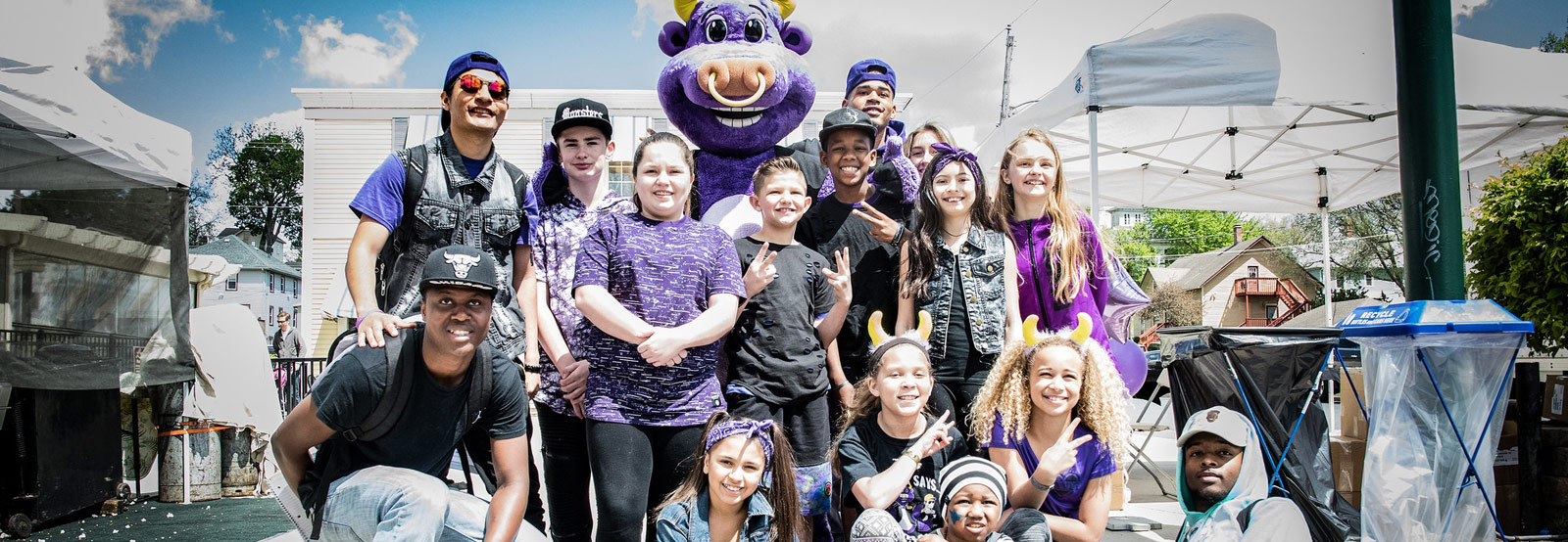 Photo showing Pete the Purple Bull with members of Reflex Dance and school kids from the Quad Cities